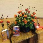 Bloemstuk 16 juli 2017 Op deze zondag maken Anthe Lise, Benjamin en Sytse de overstap  van de kinderkerk naar de jeugdkerk. Wat neem je mee voor onderweg? Wat stop je in je rugzak? Ook al kom je een keer in een storm, of gooi je je netten aan de verkeerde kant,  Jezus pakt jou bij de hand en helpt je weer met bolle zeilen en gevulde netten  de goede kant op. Een bloemstuk in de kleur oranje,  symbool voor humor, kracht, creativiteit, plezier, warmte en samenzijn!