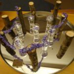 Bloemstuk 28 februari 2021: Een ander te drinken geven. De glazen zijn deze week gevuld met water waarin de bloemen van de hyacint drijven. De blauwe kleur verwijst naar de verbinding tussen hemel en aarde. De vorm van het open hart wordt geaccentueerd door een geregen ketting van hyacintennagels