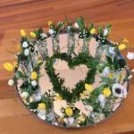 Pasen 2021: Wie God liefheeft, heeft ook de ander lief. Het hart is vol met bloemen. De stammen en stenen zijn vervangen door meer vazen. De vprm van het hart wordt geaccentueerd door buxus takjes. Zo verbinden we de tijd voor Pasen met Pasen.